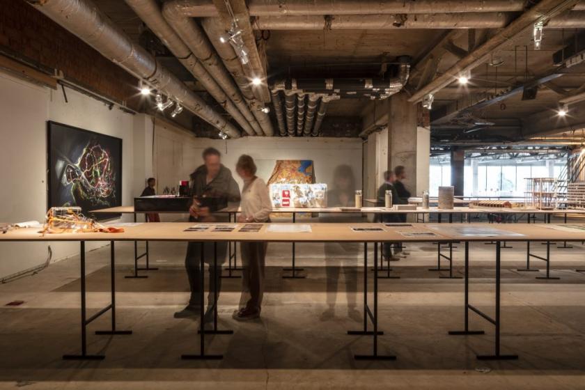 Mensen bekijken de tentoongestelde voorwerpen op de expo 'You Are Here'