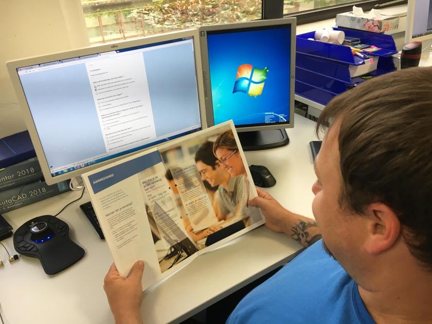 Een cursist van een VDAB-opleiding bekijkt een brochure.