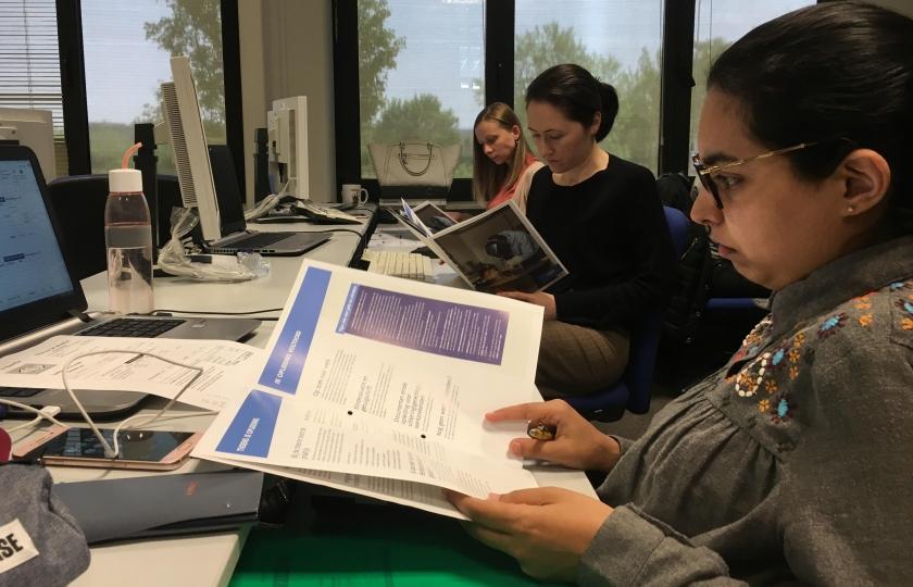 Cursisten van een VDAB-opleiding lezen een brochure.