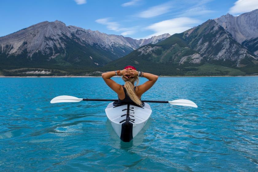 Vrouw die aan het kajakken is op een blauw bergmeer