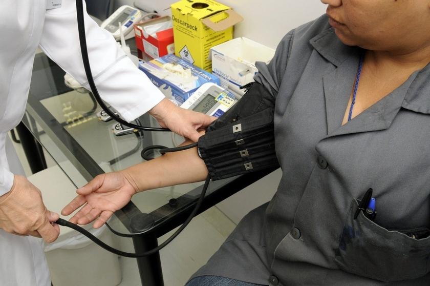 Verpleger neemt bloeddruk van patiënt.