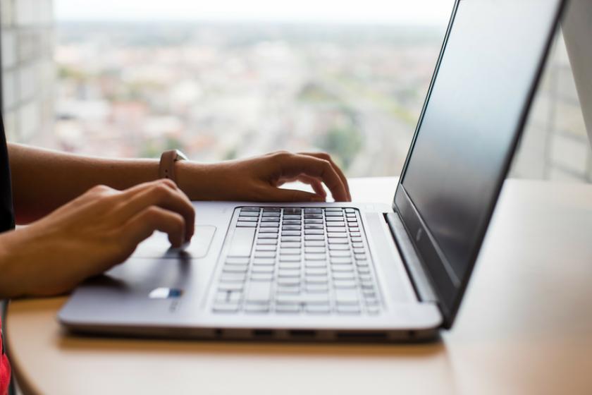 handen rusten op toetsenbord van laptop