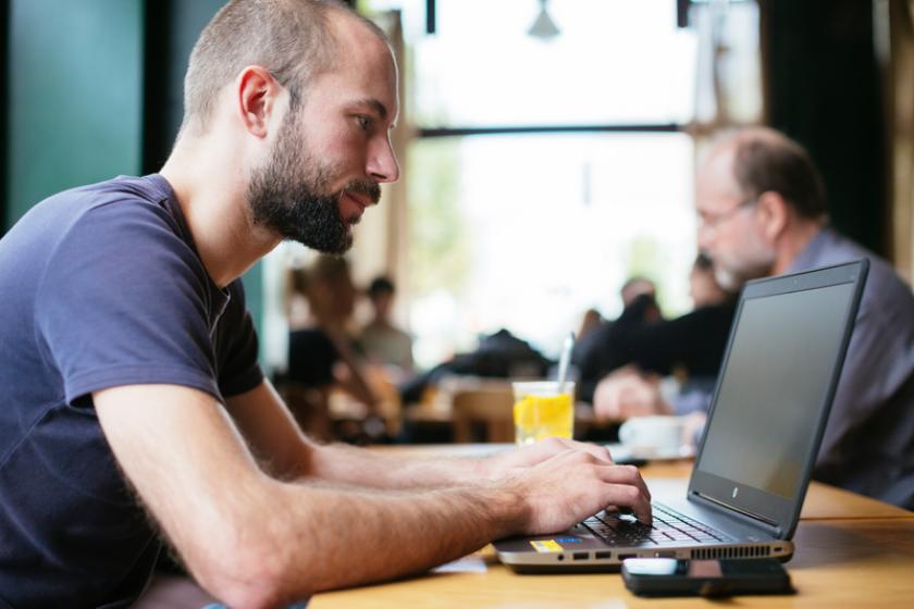 Man werkt in een café op zijn laptop.