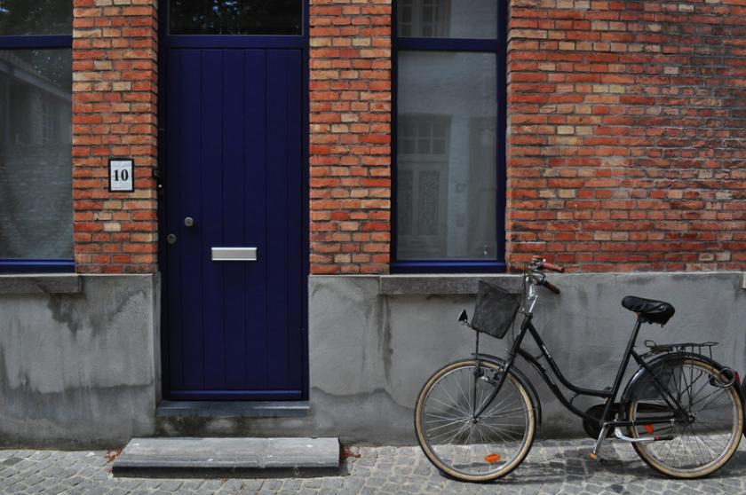 Aan het huis met nummer 10 en een donkerblauwe voordeur staat een fiets.
