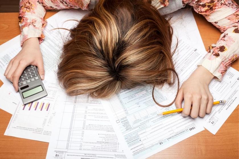 Vrouw die met hoofd op haar bureau ligt boven een stapel papieren