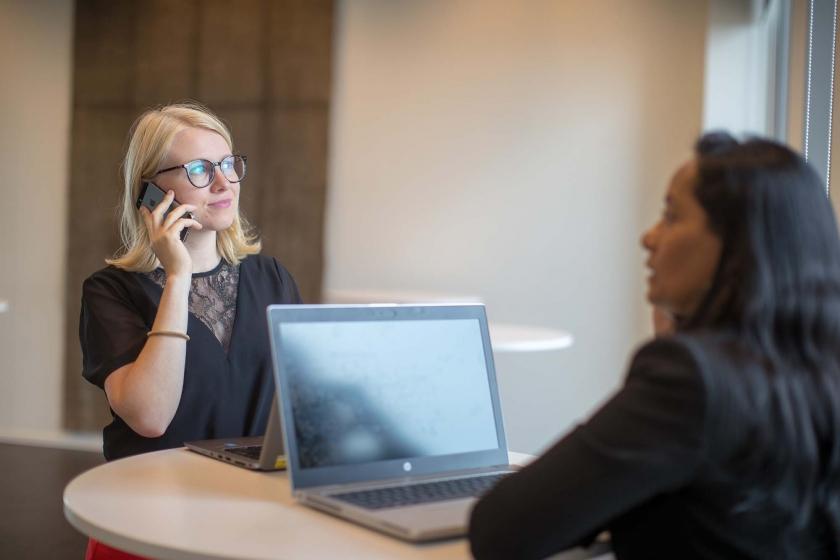 Vrouw met laptop en vrouw die telefoneert aan statafel