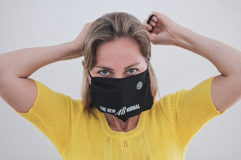 Vrouw met mondmasker met daarop de tekst 'the new abnormal'