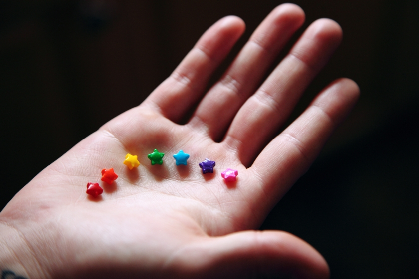 Foto van hand met kleine sterretjes in regenboogkleuren