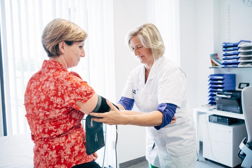 Verpleegster meet bloeddruk van patiënt