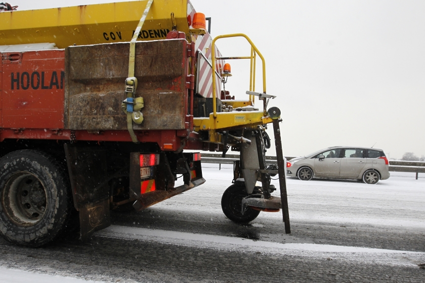 Strooiwagen aan het werk op een besneeuwde weg