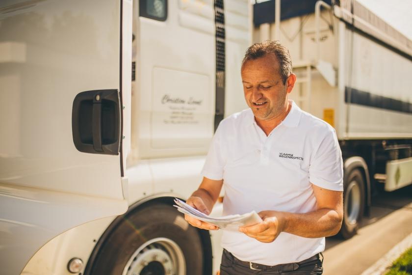 Een wegeninspecteur bekijkt enkele documenten.