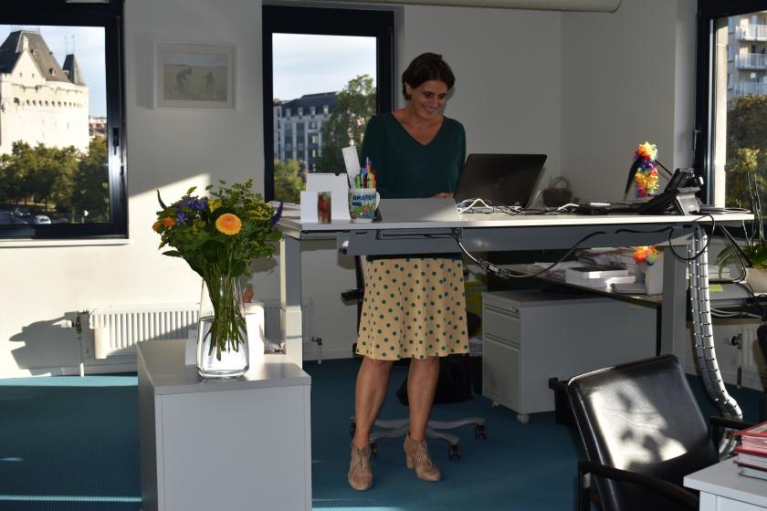 Leidend ambtenaar Katrien Verhegge van Kind en Gezin werkt rechtstaand aan haar bureau (Foto: Kind en Gezin)