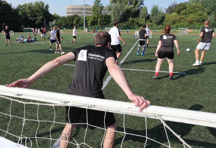 Ambtenaars spelen voetbal op Sportdag