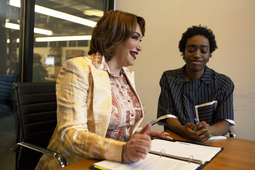 Twee collega's, een transgender vrouw en een non-binair persoon, lachend tijdens een overleg op het werk.