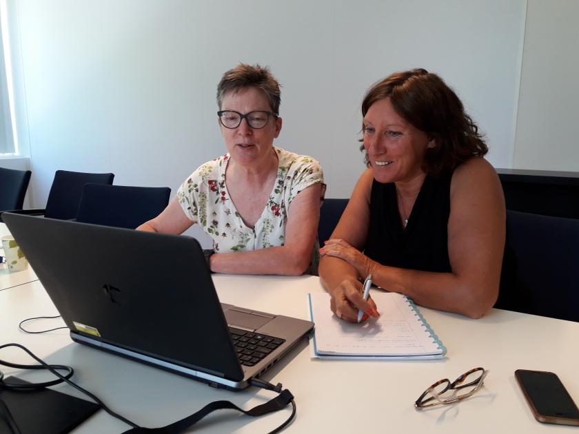 Carina en Marianne kijken samen op een laptop